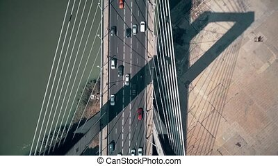 Aerial top-down view of cars moving along cable-stayed...