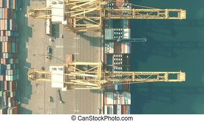 Aerial top down view of container terminal cranes and cargo ship in the port
