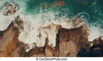 Aerial top down view of foamy sea surf on rocks - Aerial top...