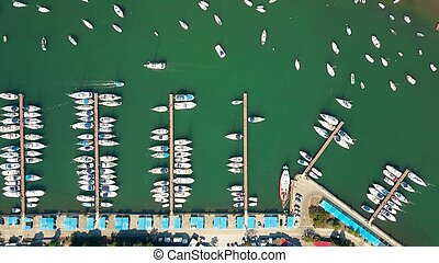 Aerial top down view of parked boats, motorboats and sailboats at marina piers