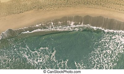 Aerial top down view of sea surf on sand beach with many...