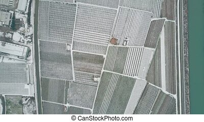 Aerial top down view of snow covered fields and farms in...