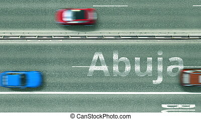 Aerial top-down view of the road. Cars reveal Abuja text. Travel to Nigeria 3D rendering