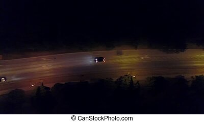 Aerial top down view shot of a rural European car road and roundabout at night