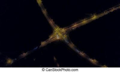 Aerial top down view time lapse of a rural European car road roundabout at night