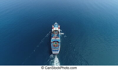 Aerial top drone view of luxury large cruise ship with pool sailing full speed on open blue water,