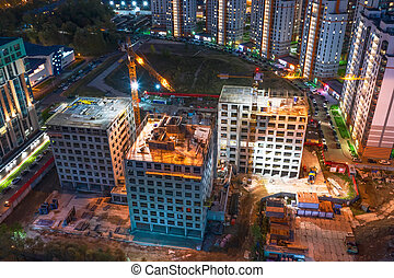 Aerial top night view large-scale construction of a residential complex with a view of construction cranes.