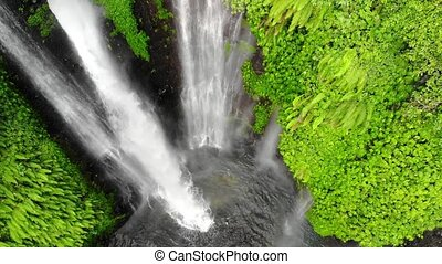 Aerial top of view on amazing waterfall on tropical island in Bali. slow motion.