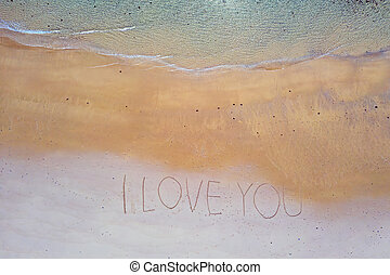 Aerial top shot from ocean waves and handwritten I love you at the beach