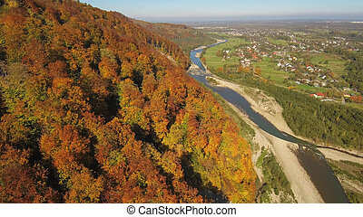 Aerial, top view from Drone: flying over the mountain with forest and river.