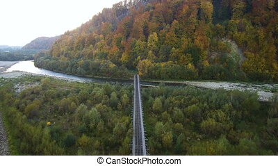 Aerial, top view from Drone: Railway through the river into the forest.