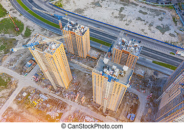 Aerial top view large-scale construction of a residential complex with a view of construction cranes.