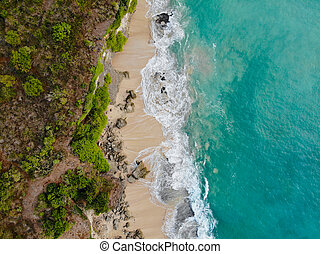 Aerial top view of a beautiful sandy beach with rocks, Bali