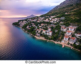 Aerial top view of a village located on a mountain by the sea at sunset in Croatia