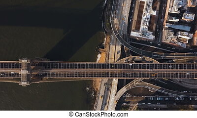Aerial top view of Brooklyn bridge through the East river and road junction on Manhattan side in New York, America.