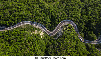 Aerial top view: of cars driving on zig zag winding mountain road