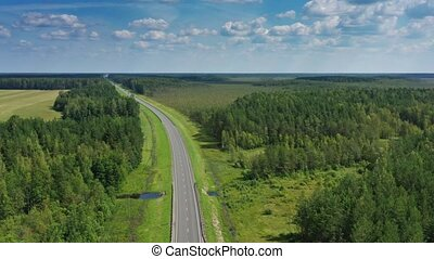 Aerial top view of country road in forest
