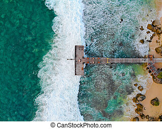 Aerial top view of dock over tropical blue water and sand beach