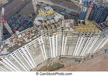 Aerial top view of high-rise residential buildings under construction and cranes.