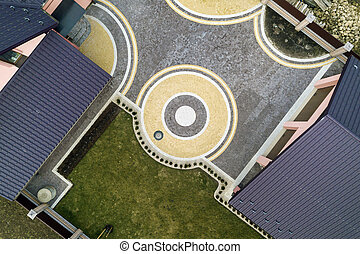 Aerial top view of house shingle roof on background of green lawn and colorful paved yard with geometrical abstract pattern.
