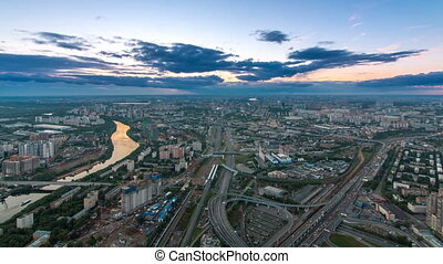 Aerial top view of Moscow city day to night transition timelapse after sunset. Form from the observation platform of the business center of Moscow City. Moscow river and traffic on roads at summer day