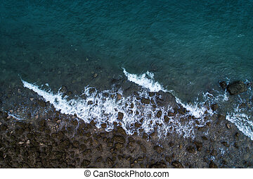 Aerial top view of ocean waves and Rock coast.