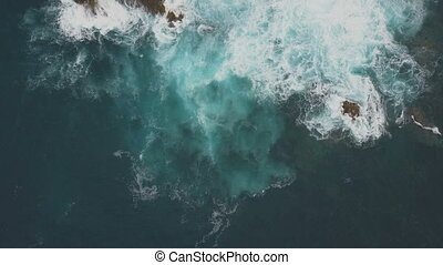 Aerial top view of ocean waves breaking on dark rocks, Canary Islands, Tenerife, Spain