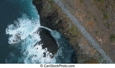 Aerial top view of ocean waves breaking on dark rocks on black sand beach, Canary Islands, Tenerife, Spain