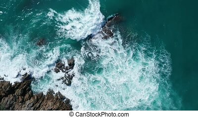 Aerial top view of ocean's beautiful waves and rocky coast
