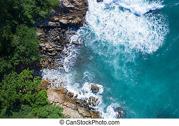Aerial top view of ocean's beautiful waves and rocky coast with greenery
