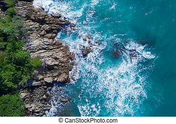 Aerial top view of ocean's beautiful waves crashing on the rocky island coast
