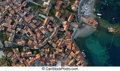 Aerial top view of red roofs in small city by blue sea in Croatia.