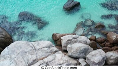 Aerial top view of rocks with crystal clear lagoon sea