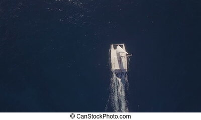 Aerial top view of sailing white yacht in empty ocean blue water, Mauritius Island