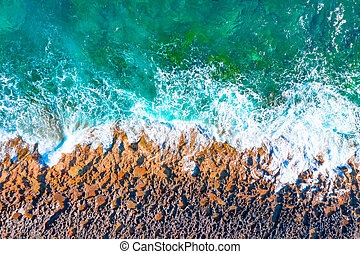 Aerial top view of sea waves hitting rocks on the beach.