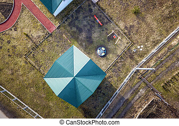 Aerial top view of shingle roof of kindergarten or modern school building on colorful playground in sunny yard background,