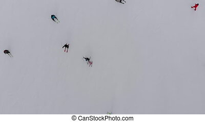 Aerial Top view of Skiers go Down the Ski Slope on Ski Resort in Mountains