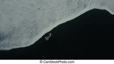 Aerial top view of the waves with foam on black volcanic beach in Iceland. Young couple walking near the sea.
