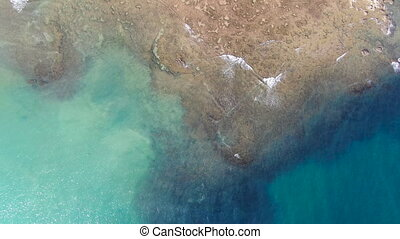 Aerial top view of turquoise clear sea water with coral reef.