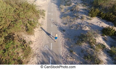 Aerial - Top view of woman in a blue dress walking on wood road.