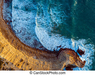 Aerial top view on rock cliffs and waves