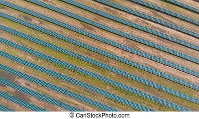 Aerial Top view on Solar Power Station in Green Field on Sunny day. Drone fly over Solar Farm. Lot of Solar Panels Stand in Row for Power Production. Renewable green energy. Alternative energy sources