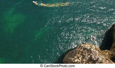 Aerial. Tourists entertained at boating and kayaking in the bay Ponta de Piedade.