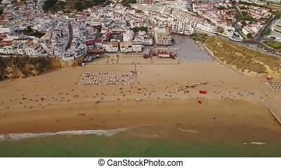 Aerial. Tourists on the sandy beach of Albufeira filmed from sky.
