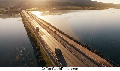 Aerial tracking shot of unknown cars moving along the dam at...