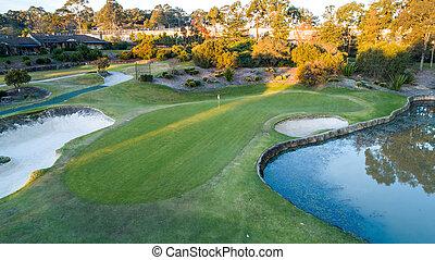 aerial udsigt, i, golf kurs, grønne, hos, flag, bunkere, og, dæmning, vand hazards, omgivet, af, træer, ind, baggrund