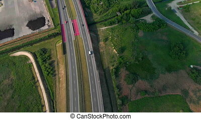 Aerial vertical shot. Cars driving by the road. Traffic on the highway. 4K footage from drone.