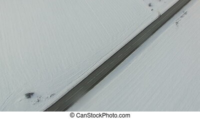 Aerial vertical shot of truck and cars driving winter road in snowy field.