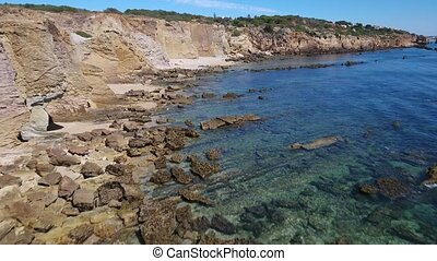 Aerial. Video footage of the cliffs on the beach Arrifes, Sao Rafael.