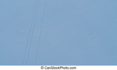 Aerial video of elecric wires and small power line pylons in winter. Top view